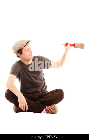 Young smiling man holding paint brush against white background - Stock Photo