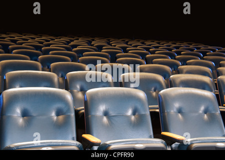 Backs of empty blue seats in a movie theater.