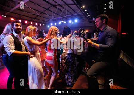 Tourists dancing over traditional Greek music during a variety show in a Taverna restaurant near Hersonissos also - Stock Photo
