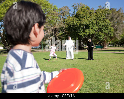Arab family playing frisbee at the park, boy holding plastic disc. - Stock Photo