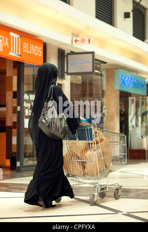 Rear view of arab woman with shopping cart walking at the mall. - Stock Photo
