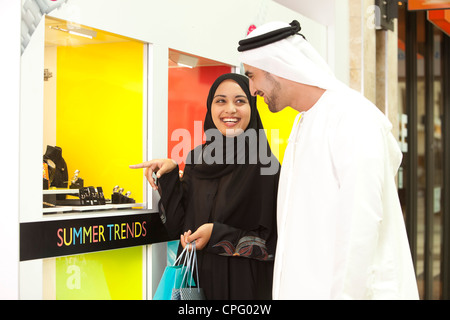 Arab couple with shopping bags standing in front of a jewelry shop, woman pointing. - Stock Photo
