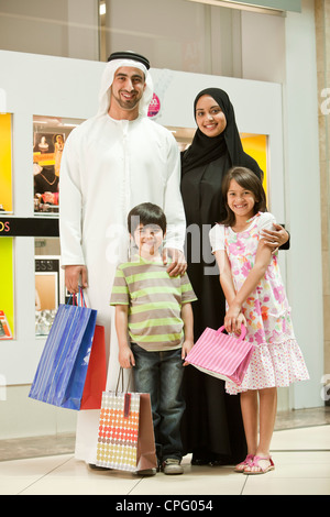 Portrait of arab family standing in the shopping mall, smiling. - Stock Photo