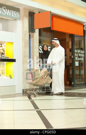 Young arab couple with shopping cart walking in the mall. - Stock Photo