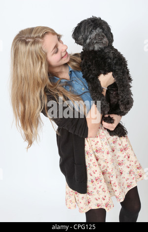 Young teenage girl standing holding a cute black dog. - Stock Photo