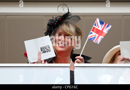 Woman with a small UK flag and a Royal Ascot song book at horse races, Ascot, UK - Stock Photo