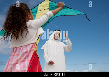 Arab father and daughter with kite at the beach. - Stock Photo