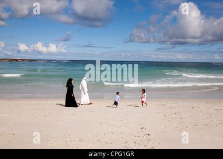 Arab family at the beach, children running on the sand. - Stock Photo