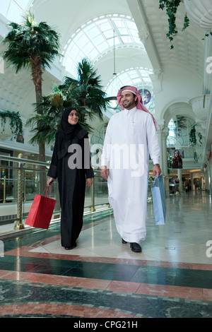 Arab couple with shopping bags walking in the mall. - Stock Photo