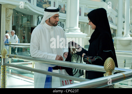 Arab couple in shopping mall, woman holding a scarf. - Stock Photo