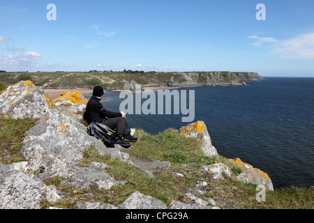Walker Enjoying the View Over Three Cliffs Bay From Great Torr Penmaen Burrows Gower Wales UK - Stock Photo