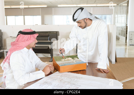 Two arab businessmen discussing over blueprint. - Stock Photo