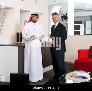 Two businessmen having coffee in the office lobby, smiling. - Stock Photo