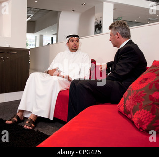 Two businessmen talking on sofa in office. - Stock Photo
