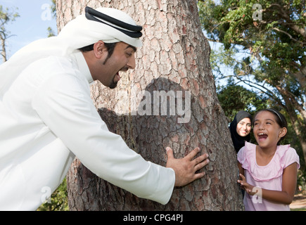 Arab family playing hide and seek in the park. - Stock Photo
