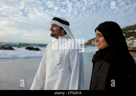 Arab couple standing by the beach, smiling. - Stock Photo