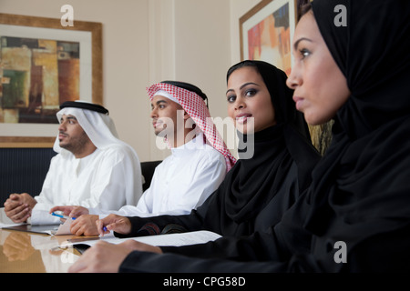 Arab business people in meeting, portrait of woman smiling. - Stock Photo