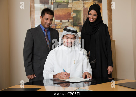 Arab businessman signing document, two colleague standing on the side. - Stock Photo