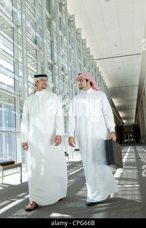 Two arab businessmen talking while walking in office hallway. - Stock Photo