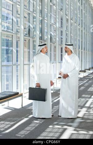 Arab businessmen talking in office hallway. - Stock Photo