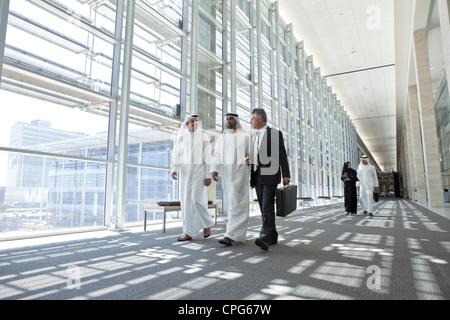 Three businessmen talking in office hallway, arab business man and businesswoman walking in background. - Stock Photo
