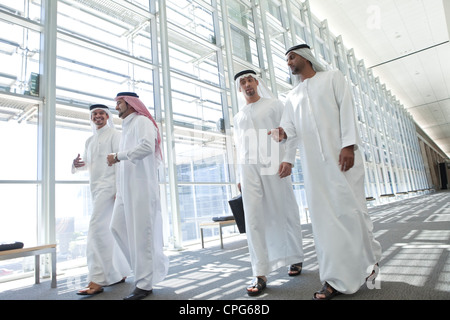 Four arab businessmen talking while talking in the office hallway. - Stock Photo