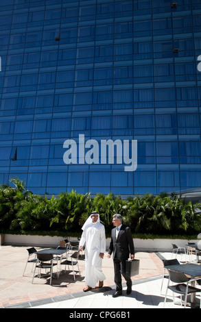 Arab businessman and western businessman walking in front of office building. - Stock Photo