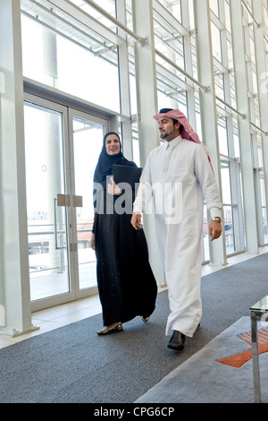 Arab businessman and businesswoman talking while walking in office hallway. - Stock Photo