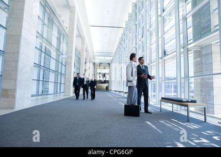 Two businessmen talking in office hallway. Three business people walking in background. - Stock Photo