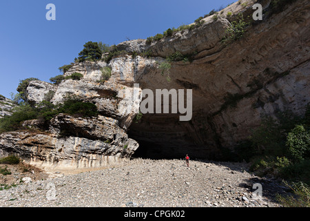 Woman standing in the dry river bed at the entrance to the cave below Minerve, Llanguedoc, Herault, France - Stock Photo