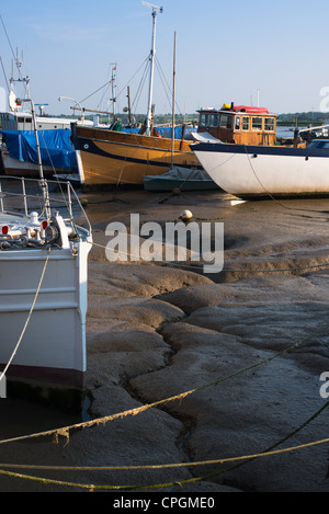 Boats in mud at low tide on River Deben estuary at Woodbridge, Suffolk, UK. - Stock Photo