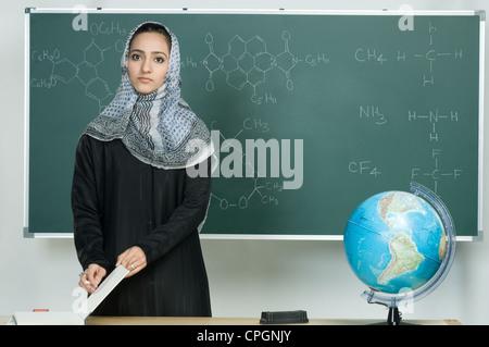 Teacher standing against board in school, portrait - Stock Photo