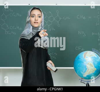 Teacher standing in front of board and pointing out - Stock Photo