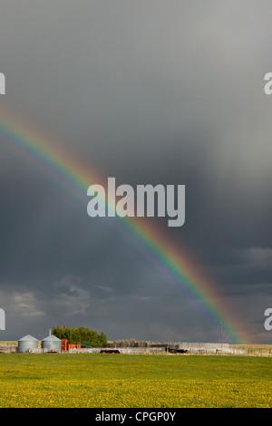 Rainbow over Canadian prairie farm - Stock Photo