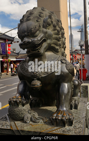 Bronze male guardian lion sculpture at the gate to Fangbang road Old Street in Shanghai Peoples Republic of China - Stock Photo