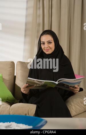 Young woman sitting on sofa, holding magazine, portrait - Stock Photo