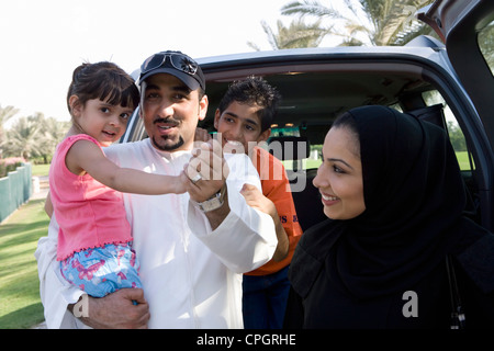 Family standing in front of car, smiling - Stock Photo