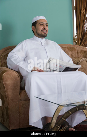 Arab man sitting in a sofa holding a newspaper - Stock Photo