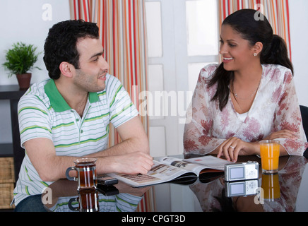 Couple talking in the dining room, sitting - Stock Photo