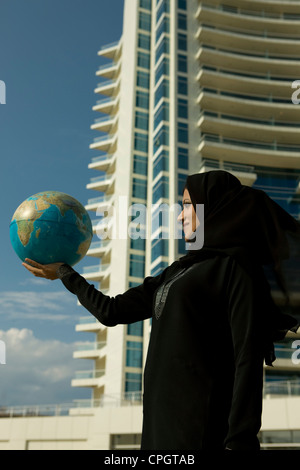 Arab woman holding a globe, standing with background of building at Dubai Marina, UAE - Stock Photo