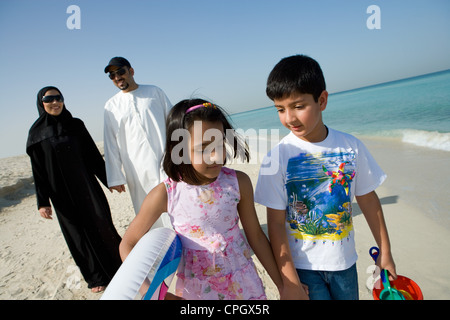 Family walking on beach, smiling - Stock Photo