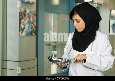 Female doctor holding medical tray and forceps. - Stock Photo