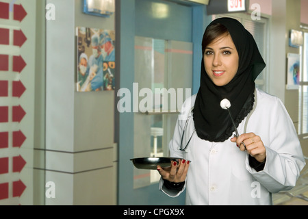 Female doctor holding medical tray and forceps,portrait. - Stock Photo