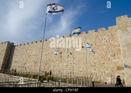 View of City Walls with orthodox jews and Israeli flag. Jerusalem Old City. israel. - Stock Photo