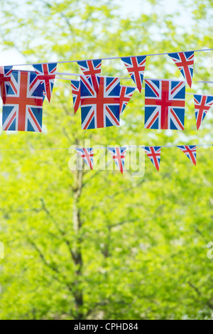 Union Jack flag bunting in front of sunlit trees - Stock Photo