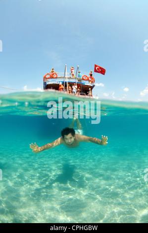 Split level, man diving next to the tour boat, Cleopatra island (Sedir Island), Aegean Sea, Turkey - Stock Photo