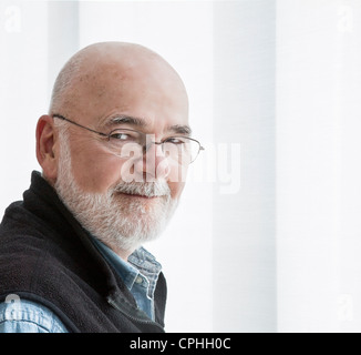 Head shot of Caucasian senior male, head turned sideways looking at the camera.  He is dressed casually and has - Stock Photo