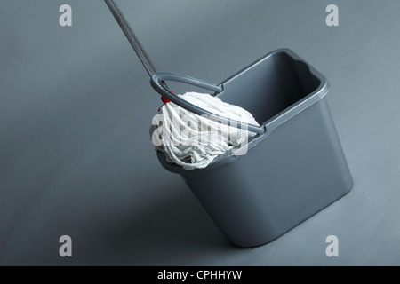 Industrial mop and bucket on grey background - Stock Photo
