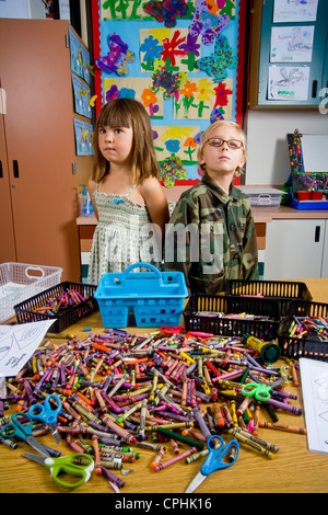 Kindergarten children in San Clemente CA contemplate a table full of classroom objects including crayons and worksheets - Stock Photo
