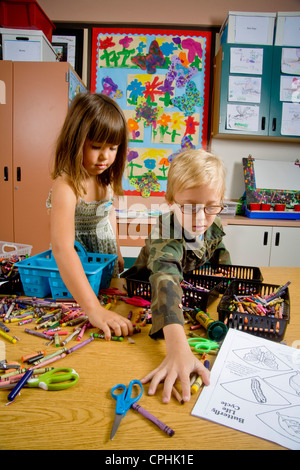 Kindergarten children in San Clemente CA collect and organize a table full of classroom objects including crayons - Stock Photo